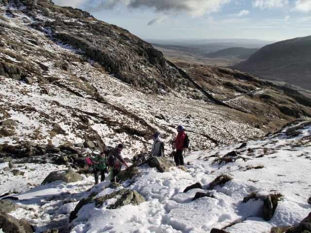 Skiers and snowboarders carrying their gear above Afon Lloer