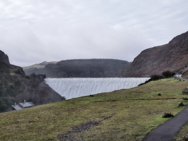 The dam at Caban Coch Reservoir, with water overflowing the top
