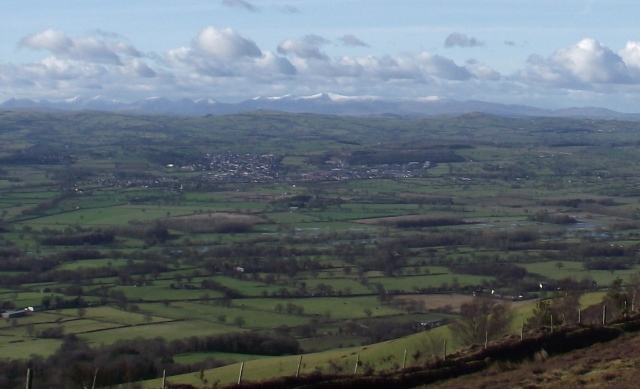 The snow-capped mountains of Snowdonia, with the town of Denbigh in the middle ground